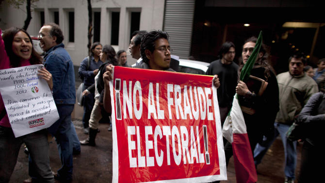 """A man holds up a sign that reads in Spanish """"No to electoral fraud"""" outside a hotel where Mexican presidential candidate Andres Manuel Lopez Obrador of the Democratic Revolution Party (PRD), gave a news conference in Mexico City, Monday, July 2, 2012. After official results showed Enrique Pena Nieto of the Institutional Revolutionary Party (PRI) winning 38 per cent of the vote with more than 92 per cent of the votes counted, Lopez Obrador has not conceded Sunday's elections,  telling his  supporters Monday evening that, """"We can't accept a fraudulent result,"""" a reference to his allegations that Pena Nieto exceeded campaign spending limits, bought votes in some states and benefited from favorable coverage in Mexico's semi-monopolized television industry. (AP Photo/Alexandre  Meneghini)"""