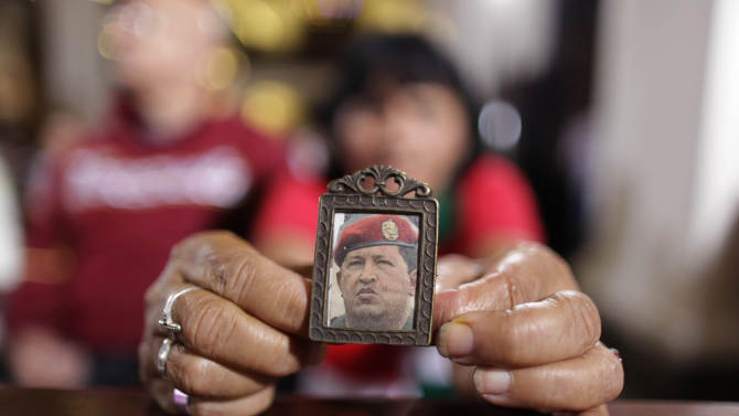 """A woman holds an image of Venezuela's President Hugo Chavez as people gather to pray for him at a church in Caracas, Venezuela, Monday, Dec. 31, 2012. Venezuela's President Hugo Chavez is confronting """"new complications"""" due to a respiratory infection nearly three weeks after undergoing cancer surgery, his Vice President Nicolas Maduro said Sunday evening in Cuba as he visited the ailing leader for the first time since his operation. (AP Photo/Ariana Cubillos)"""
