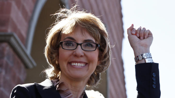 Former Rep. Gabrielle Giffords smiles as she raises a fist pump to the crowd as she, her husband Mark Kelly, and a number of other Tucson mass shooting victims returned to the site of a shooting that left her critically wounded to urge key senators to support expanded background checks for gun purchases, Wednesday, March 6, 2013, in Tucson, Ariz. (AP Photo/Ross D. Franklin)