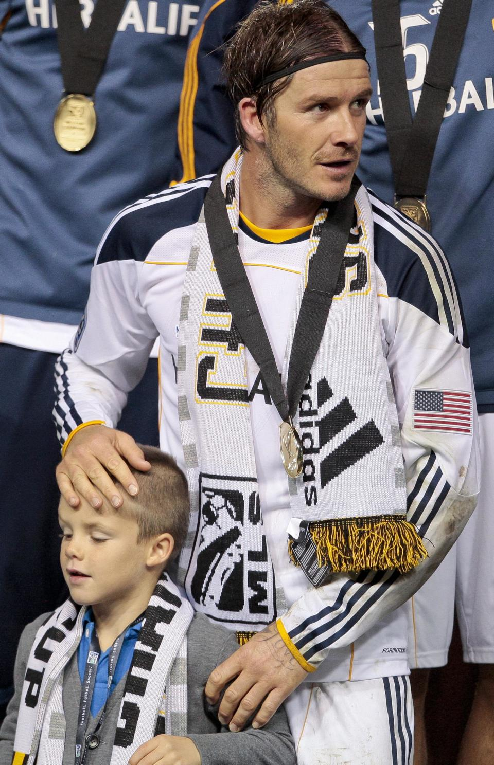 Los Angeles Galaxy midfielder David Beckham stands with his son Cruz after the Galaxy defeated the Houston Dynamo to win the MLS Cup championship soccer match, Sunday, Nov. 20, 2011, in Carson, Calif. (AP Photo/Bret Hartman)