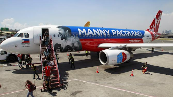 Passengers disembark the AirAsia Philippines Airbus A320 plastered with the image of Filipino boxer Manny Pacquiao as they arrive from Cebu at the Domestic airport in Pasay city, metro Manila