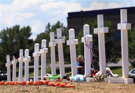 "Crosses are seen at a memorial for victims behind the theater where a gunman opened fire on moviegoers in Aurora, Colorado July 22, 2012. President Barack Obama travels to Colorado on Sunday to meet families bereaved after a ""demonic"" gunman went on a shooting rampage at a movie theater in a Denver suburb, killing at least 12 people and wounding 58."