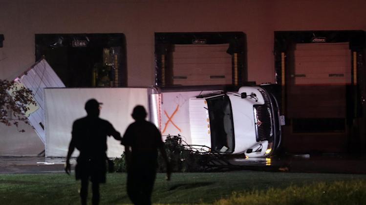 People walk near an overturned truck in an industrial park after strong storms moved through the area Friday, May 31, 2013, in St. Louis. (AP Photo/Jeff Roberson)
