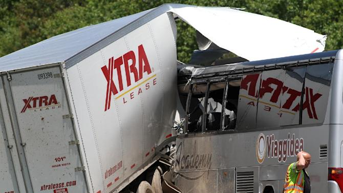 A man walks near the scene of a fatal collision between a tractor-trailer and a tour bus on Interstate 380 near Tobyhanna, Pa., Wednesday, June 3, 2015. Multiple people were killed and more than a dozen were sent to hospitals. (Jake Danna Stevens/The Times & Tribune via AP)