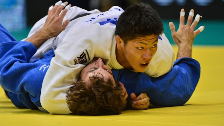 Japan's Riki Nakaya (top) competes with Ukraine's Volodymyr Soroka in the Men's 73kg category of the IJF World Judo Championship in Rio de Janeiro, Brazil, on August 28, 2013