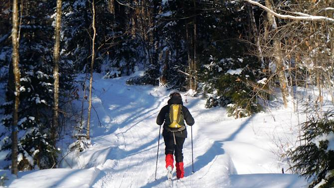 This December 2012 photo shows Donna Lawlor cross-country skiing on the Lodge to Lodge trail between camps at the Appalachian Mountain Club's backcountry wilderness lodge near Greenville, Maine. In winter, visitors can reach the lodges and cabins only by cross-country skiing in.  (AP Photo/Lynn Dombek)