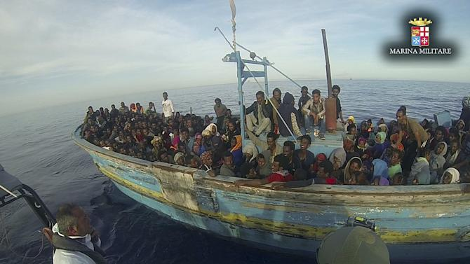Handout shows migrants sitting in their boat during a rescue operation by Italian navy ship Vega off the coast of Sicily