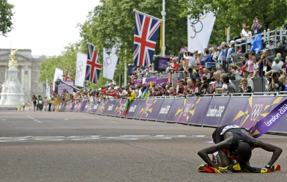 Stephen Kiprotich of Uganda celebrates after he crossing the finish line to win the men's marathon at the 2012 Summer Olympics in London, Sunday, Aug. 12, 2012. (AP Photo/Luca Bruno)