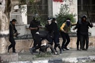 Egyptian riot police detain a man during clashes on Omar Makram street, off Tahrir Square, on November 28, in Cairo. A divisive panel boycotted by liberals and Christians was set to vote on a draft new Egyptian constitution, amid mounting protests over President Mohamed Morsi's assumption of sweeping powers