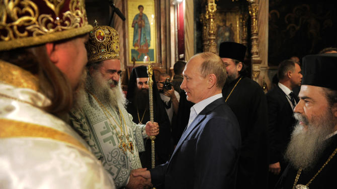 Russian President Vladimir Putin, center, shakes hands with Archbishop of Jordan Theophylactos, as the Patriarch of Jerusalem Theophilos III, stands on the right , during a visit to the Holy Sepulcher, in Jerusalem, Tuesday, June 26, 2012. (AP Photo/RIA-Novosti, Alexei Druzhinin, Presidential Press Service)
