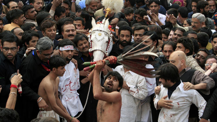 A Pakistani Shiite Muslim flagellates himself with swords attached with a chain during a Muharram procession in Lahore, Pakistan on Saturday, Nov. 24, 2012. Muharram is a month of mourning in remembrance of the martyrdom of Imam Hussein, the grandson of Prophet Mohammed. (AP Photo/K.M. Chaudary)