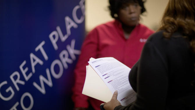 FILE - In this Thursday, Nov. 14, 2013, file photo, Jimmetta Smith, of Lithonia, Ga., right, the wife of a U.S. Marine veteran, holds her resume while talking with Rhonda Knight, a senior recruiter for Delta airlines, at a job fair for veterans and family members at the VFW Post 2681, in Marietta, Ga. Payroll processor ADP issues its report on job growth among private companies in December on Wednesday, Jan. 8, 2014. (AP Photo/David Goldman, File)