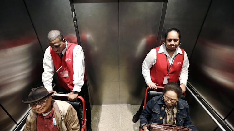 In this Tuesday, Oct. 22, 2013 photo, wheelchair attendants Erick Conley, left, and Sesilia Vaitele assist a pair of passengers heading to an overseas flight at Seattle-Tacoma International Airport, in SeaTac, Wash. There's a campaign underway to raise the minimum wage to $15 for the more than 6,300 jobs at Seattle's largest airport. If approved by voters on Nov. 5, the wage rate, as well as sick days and other benefits, would only apply to the city of SeaTac. The vote is one of the latest flashpoints in the national debate over the minimum wage after fast food workers and others held a series of summertime rallies to bring attention to their struggle to earn a living. (AP Photo/Elaine Thompson)