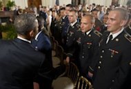 <p>US President Barack Obama shakes hands with active duty US service members, after they became US citizens during a naturalization ceremony in the East Room of the White House in Washington, DC, July 4, 2012.</p>