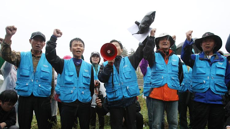 North Korean defectors shout slogans as police officers block their planned rally on a road in Paju near demilitarized zone, South Korea, Monday, Oct. 22, 2012. South Korea has banned activists from launching propaganda leaflets to North Korea after North Korea threatened to attack.(AP Photo/Ahn Young-joon)