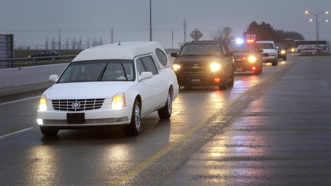 A hearse containing Chris Kyle's casket leads a motorcade leaving the Multi-Purpose Stadium, in Midlothian, Texas, Tuesday, Feb. 12, 2013 for the 200-mile journey to Austin, where Kyle will be buried at the Texas State Cemetery. Some 7,000 people attended a two-hour memorial service for Kyle at Cowboys Stadium in Arlington on Monday. Kyle and his friend Chad Littlefield were shot and killed Feb 2. at a North Texas gun range. (AP Photo/Star-Telegram, Max Faulkner)