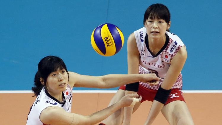 Kimura and Shinnabe of Japan look at the ball as they attempt to receive during their FIVB Women's Volleyball World Grand Prix 2014 final round match against China in Tokyo