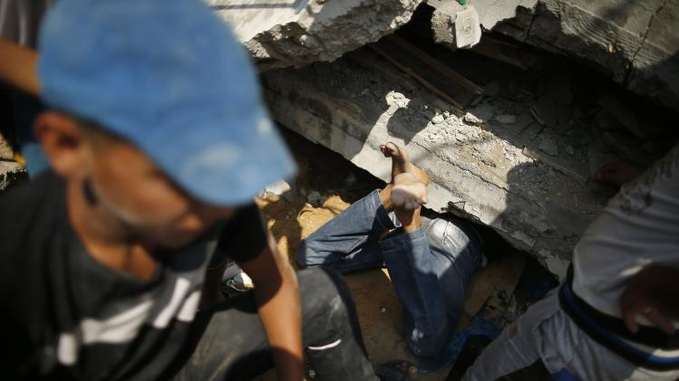 Palestinians search for belongings under the rubble of a residential building, which police said was destroyed in an Israeli air strike, in Gaza City