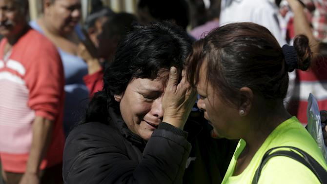 A family member of an inmate reacts while standing with others outside the Topo Chico prison in Monterrey