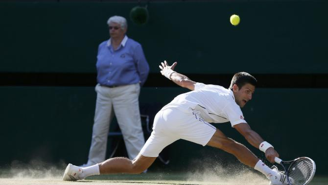 Novak Djokovic of Serbia hits a return against Roger Federer of Switzerland during their men's singles finals tennis match on Centre Court at the Wimbledon Tennis Championships in London