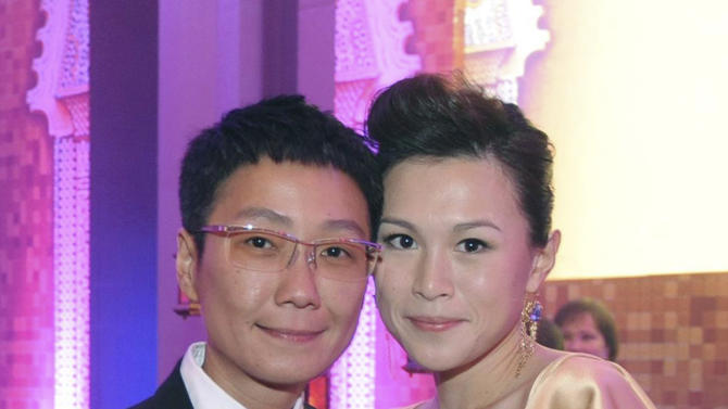 "In this undated photo, Gigi Chao, right, daughter of the Hong Kong property tycoon Cecil Chao, poses with her partner Sean Eav at an event in Hong Kong. The daughter of the prominent Hong Kong tycoon who has offered $65 million to any man who can woo her away from her lesbian partner says she's not upset with her father. Gigi says she's on ""very loving terms"" with her father. He made world headlines this week when he offered the 500 million Hong Kong dollar marriage bounty after learning that his daughter had eloped with her partner to France.  (AP Photo)"