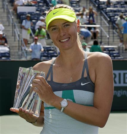 Sharapova poses with a smaller replica trophy after defeating Wozniacki in their women's singles final match at the BNP Paribas Open WTA tennis tournament in Indian Wells