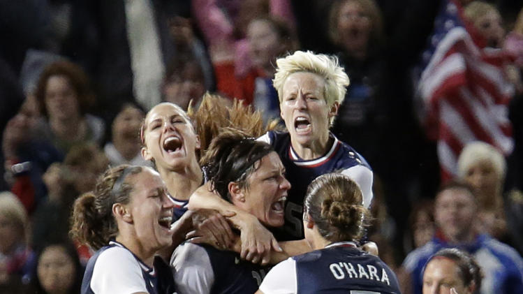 United States' Abby Wambach, center, celebrates her penalty goal with her teammates during the semi final women's soccer match between the USA and Canada at the 2012 London Summer Olympics, in Manchester, England, Monday, Aug. 6, 2012. (AP Photo/Hussein Malla)