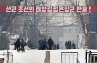 North Korean workers pass beneath a banner saying, &quot;The Great General Kim Jong-Un&quot; at the North Korean town of Sinuiju across from the Chinese city of Dandong, on February 13, 2013. Already under fire for its latest nuclear test, North Korea has been making preparations at a launchpad that could pave the way for firing a long-range missile, a US think tank said Thursday