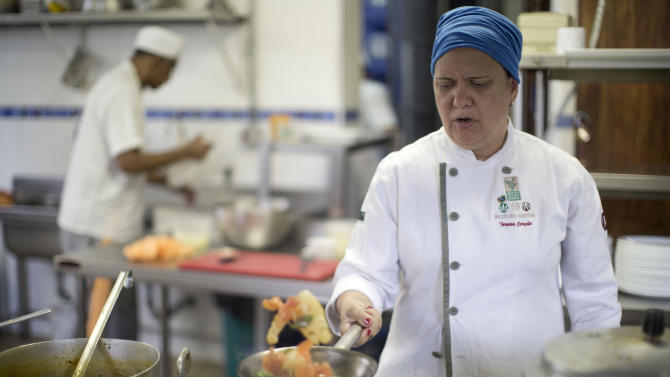 In this photo taken Friday, Dec. 14, 2012, Chef Teresa Corcao prepares a dish made with the manioc root, at the O Navegador restaurant in Rio de Janeiro, Brazil. With its starched white tablecloths and stately crystal chandeliers, the upscale restaurant doesn't look like the birthplace of a revolution. But it's here that the manioc root, long the staple food of the Brazilian poor, is making its entree into the elite world of haute gastronomy. (AP Photo/Felipe Dana)