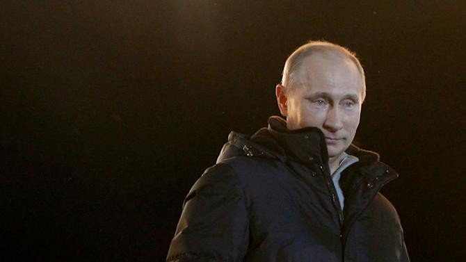 Russian Prime Minister and presidential candidate Vladimir Putin, left,  has tears in his eyes as he emotionally reacts at a massive rally of his supporters at Manezh square outside Kremlin, in Moscow, Russia, Sunday, March 4, 2012.  Putin has claimed victory in Russia's presidential election, thanking his supporters for helping foil foreign plots aimed to weaken the country, an election which the opposition and independent observers say has been marred by widespread violations.  (AP Photo/Ivan Sekretarev)
