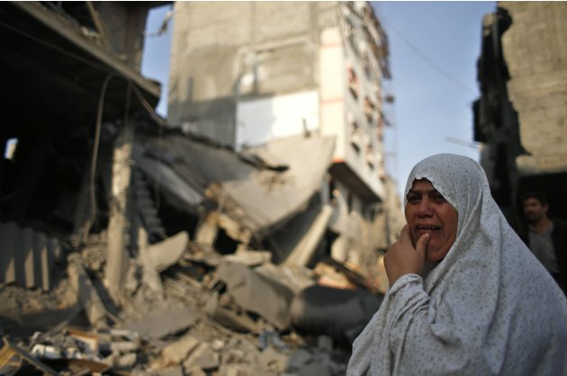 A Palestinian woman reacts in front of a destroyed house after an Israeli air strike in Gaza City