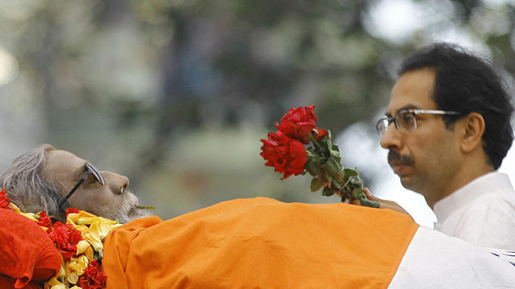 Udhav Thackeray, the son of Hindu hardline Shiv Sena party leader Bal Thackeray carries flowers past his body during his funeral in Mumbai, India, Sunday, Nov. 18, 2012. Thackeray, the extremist leader linked to waves of mob violence against Muslims and migrant workers in India, died Saturday after an illness of several weeks. He was 86. (AP Photo/Rafiq Maqbool)