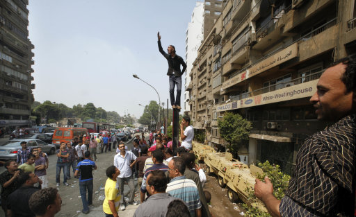 An Egyptian shouts slogans as he stands over what was a concrete wall built around a building housing the Israeli embassy a day after it was demolished by Egyptian activists in Cairo, Egypt, Saturday, Sept. 10, 2011. President Barack Obama has assured Israeli Prime Minister Benjamin Netanyahu that the U.S. is taking steps