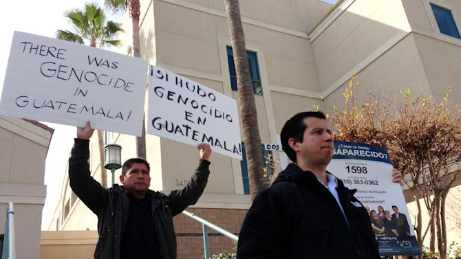 Demonstrators stand outside the federal courthouse in Riverside, Calif. on Monday, Feb. 10, 2014, after the sentencing of Jorge Sosa, a former second lieutenant of the Guatemalan army, who was convicted to ten years in prison for making false statements on his U.S. citizenship application. Sosa was a member of a special force suspected of killing at least 160 people in a remote village more than three decades ago in a massacre that still haunts its few survivors. Oscar Ramirez front right, spoke during Sosa's sentencing about how his mother and seven siblings were killed in the civil war massacre. (AP Photo/Amy Taxin)