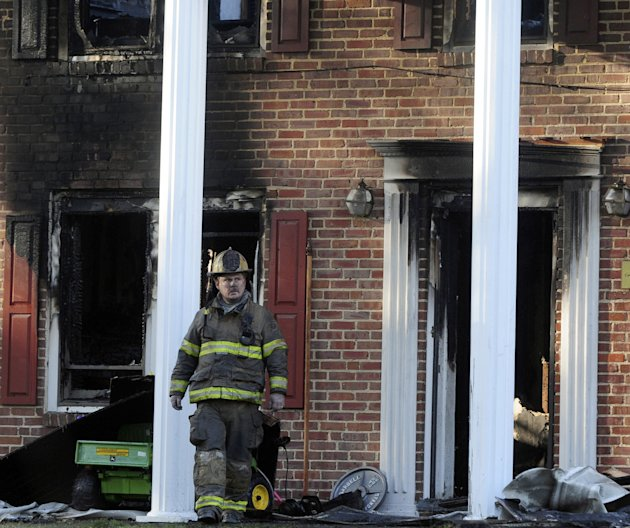 A firefighter exits the front of a heavily damaged two story home where a Special Forces soldier died trying to rescue his 2 small children during a house fire early Tuesday, March 6, 2012 in Hope Mills, N.C.. Mother Louise Cantrell, 37, was injured in the blaze that started around 2:00 am. Edward Duane Cantrell, 36, and his daughters, 6-year old Isabella Cantrell and 4-year old Natalia Cantrell all perished in the fire.