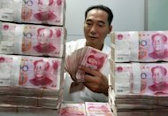 A Chinese bank staff member counts stacks of 100-yuan n in Huaibei, east China's Anhui province on August 17, 2012. Police in Sri Lanka arrested at least 114 Chinese nationals over an alleged Internet currency fraud, during a string of raids in and around Colombo, officials said