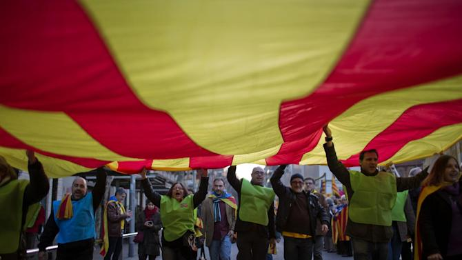 """In this photo taken on Sunday, Jan. 12, 2014, people hold a huge """"estelada"""" flag during a pro-independence event in Barcelona, Spain. After years of mass protests by Catalans demanding the right to decide whether they want to break away from Spain and form a new European nation, the wealthy northeastern region's lawmakers vote to ask permission from Spanish authorities to hold a secession referendum in November. The request eight months ahead of a Scottish independence referendum is certain to be denied by the central government in Madrid but is virtually guaranteed of generating even more separatist fervor. (AP Photo/Emilio Morenatti)"""