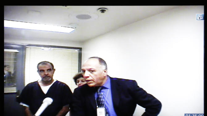 Kassim Alhimidi, left, is seen on a video screen in his video arraignment alongside his attorney, Armando Salazar, right, and an unidentified translator Tuesday, Nov. 13, 2012, in El Cajon, Calif. Alhimidi pleaded not guilty to charges that he killed his wife, Shaima Alawadi, last March. 1(AP Photo/Gregory Bull)