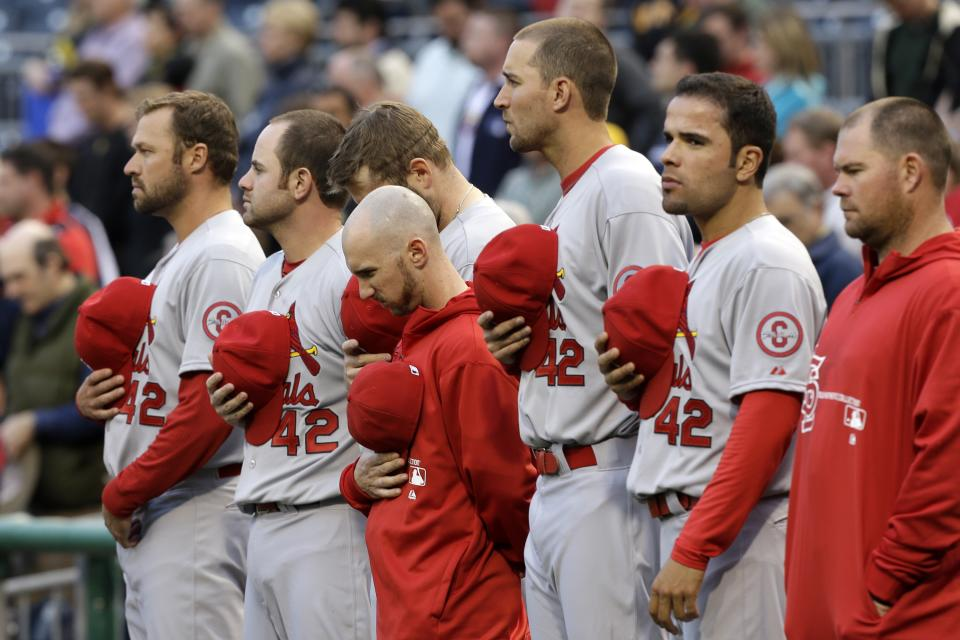 Members of the St. Louis Cardinals line up for a moment of silence following an explosion at the Boston Marathon, all wearing the No. 42 in honor of Jackie Robinson, before a baseball game against the Pittsburgh Pirates in  Pittsburgh Monday, April 15, 2013. (AP Photo/Gene J. Puskar)