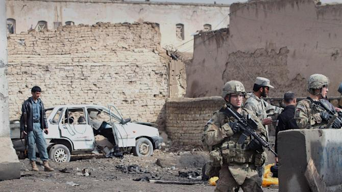 US- soldiers part of the NATO- led International Security Forces (ISAF) are seen at the scene of a suicide attack with Afghan security forces in Kandahar, south of Kabul, Afghanistan, Monday, Feb. 20, 2012. A suicide car bomber attacked the police station in southern Afghanistan's largest city on Monday, killing one police officer in the blast, officials said. (AP Photo/Allauddin Khan)