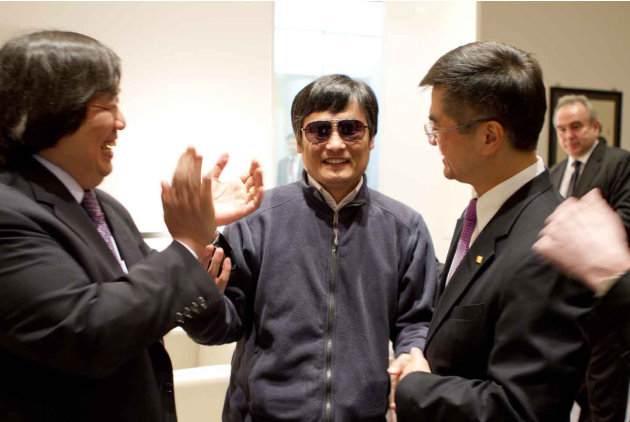 In this photo released by the US Embassy Beijing Press Office, blind lawyer Chen Guangcheng, center, holds hands with U.S. Ambassador to China Gary Locke, right, as U.S. State Department Legal Advisor