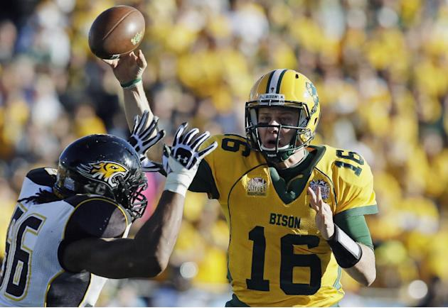 IN this Jan. 4, 2014 file photo, North Dakota State quarterback Brock Jensen gets a pass off under pressure from Towson defensive end Ryan Delaire during the FCS championship NCAA college football gam