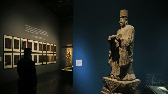 In this Monday, Sept. 15, 2014 photo, a man walks past a marble 'Spirit Way' figure at an exhibition entitled 'Ming 50 years that changed China' in British Museum in central London. This figure formed part of a 'Spirit Way' leading to the tomb of a member of the Ming imperial family. Between AD 1400 and 1450, China was a global superpower run by one family – the Ming dynasty – who established Beijing as the capital and built the Forbidden City. The exhibition, running from Sept. 18, 2014 to Jan 5, 2015, will feature a range of these spectacular objects – including exquisite porcelain, gold, jewellery, furniture, paintings, sculptures and textiles – from museums across China and the rest of the world. (AP Photo/Lefteris Pitarakis)