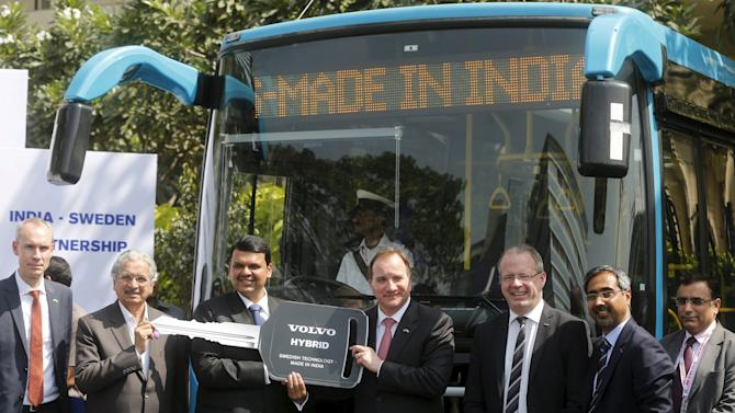 Sweden's Prime Minister Stefan Lofven and Maharashtra's chief minister Devendra Fadnavis pose in front of a Volvo hybrid bus at its launching ceremony during 'Make In India' week in Mumbai