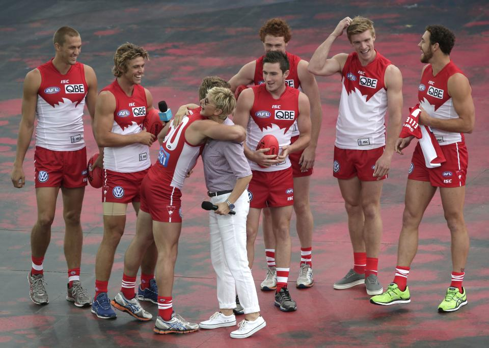 U.S. talk show host Ellen DeGeneres, fourth left, greets members of the Australian Rules Football team The Swans during a recording session of DeGeneres' show in Sydney, Australia, Saturday, March 23, 2013. (AP Photo/Rick Rycroft)