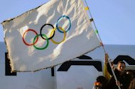 Rio de Janeiro Mayor Eduardo Paes waves the Olympic flag at the Tom Jobim International Airport in Rio de Janeiro upon arrival from London. Paes stepped off a plane carrying the flag, accompanied by Carlos Arthur Nuzman, president of the 2016 Games Organizing Committee and Rio Governor Sergio Cabral