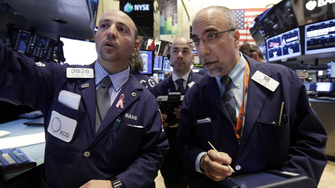 Specialist Frank Babino, left, works with traders Fred DeMarco, center, and John Liotti on the floor of the New York Stock Exchange Wednesday, March 12, 2014. U.S. stocks are heading lower for the third day in a row as investors continue to worry about slower growth in China and the lingering tensions in Ukraine. (AP Photo/Richard Drew)