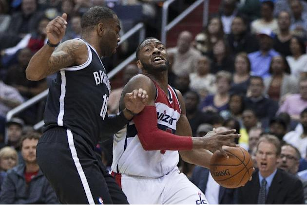 Washington Wizards guard John Wall, right, drives to the basket against Brooklyn Nets guard Marcus Thornton during the second half of an NBA basketball game Saturday, March 15, 2014, in Washington. Th