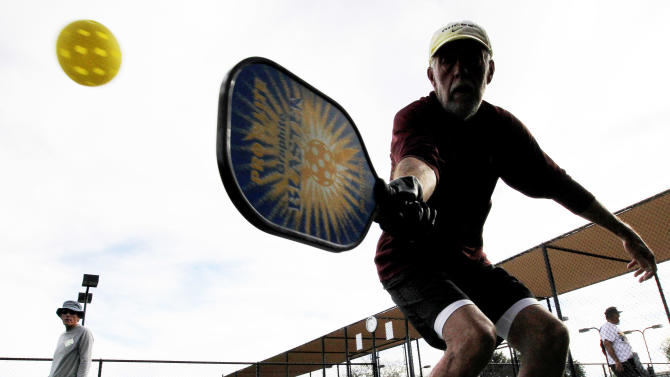 In this Monday, Dec. 3, 2012 photo, David Bone competes in a game of pickleball at Sun City West senior community in Surprise, Ariz. A hybrid of tennis, badminton and table tennis, pickleball is played on a court a quarter the size of a tennis court, with hard rackets and a variety of whiffle ball. The USAPA estimates now there are 100,000 to 150,000 pickleball players in the United States, and pickleball associations have started up in places like India and China.  (AP Photo/Matt York)