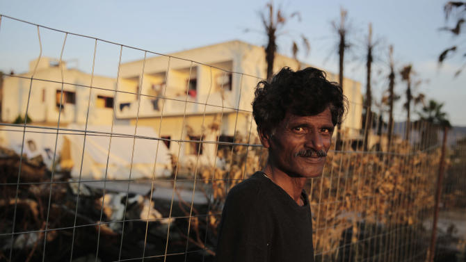 A man from Pakistan sits outside an abandoned hotel were immigrants have been given shelter at kos island, Greece, Monday, June 1, 2015. After Italy, financially crippled Greece is the main destination for refugees and economic migrants seeking a better life in the European Union. About 30,000 have arrived this year.(AP Photo/Petros Giannakouris)